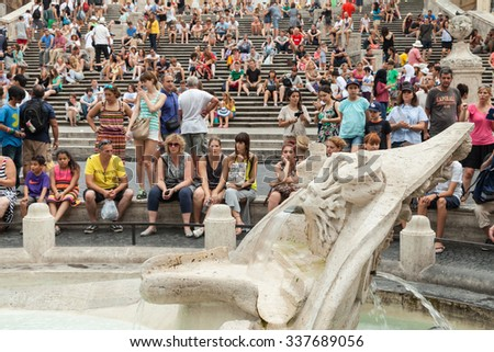 Rome, Italy - August 7, 2015: Crowd of tourists relaxing near Fontana della Barcaccia  on the Piazza di Spagna - stock photo