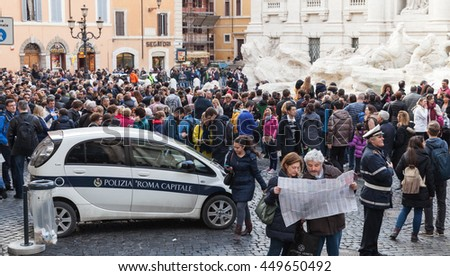 Rome, Italy - February 13, 2016: Tourists visiting the Trevi Fountain an iconic symbol of Imperial Rome. It is one of the most popular tourist attractions in Rome - stock photo