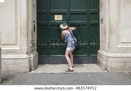 ROME, ITALY - JULY 23, 2016: Tourist peeps into the keyhole of the Villa Magistrale dei Cavalieri di Malta Rome Italy