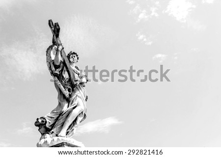 ROME, ITALY- JUNE 20: Angel with the Cross statue is located on the Ponte Sant'Angelo bridge in front of the Castel Sant'Angelo in black and white color, Rome, Italy on June 20, 2015. - stock photo