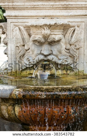 ROME, ITALY - JUNE 14, 2015: Marble fountain in the shape of the head of a man in the gardens of Villa  Borghese, Rome, Italy.