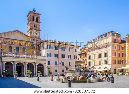 ROME, ITALY, JUNE 1, 2014: people are strolling through piazza di santa maria situated in front of the basilica with the same name in trastevere district in rome. - stock photo