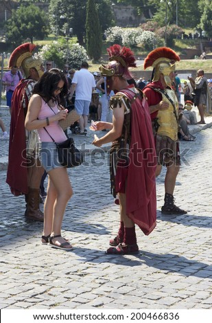 Rome, Italy - June 12, 2014 - Roman centurions offer to pose with tourists for money outside the Colosseum in Rome, Italy. Over the past few years, these men have hounded tourists for pay.