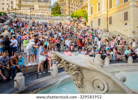 ROME, ITALY- JUNE 20, 2015: The fountain and many people visiting the steps of Piazza di Spagna, one of the most famous squares of Rome. (selective focus on fountain) - stock photo