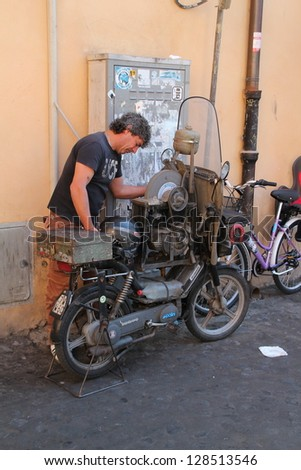 ROME, ITALY - JUNE 3: The traditional mobile knife sharpener uses a motorbike powered stone to rejuvenate wore down knives on 3 June 2011 in Rome. This is a frequent service for its inhabitants.