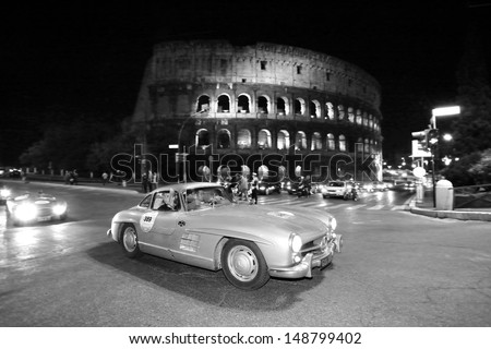 ROME ITALY - MAY 17: Mercedes Benz 300 SL W Gullwing, built in 1955, drives by the Colosseo during the 1000 Miglia historic car race, on May 17, 2013 in Rome - stock photo