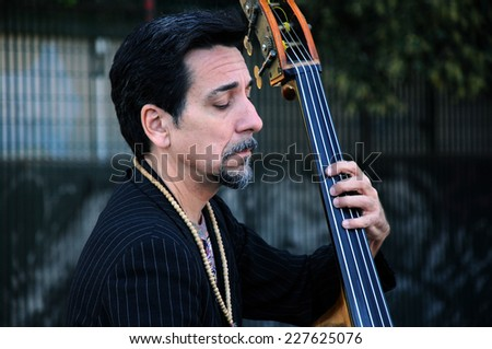 ROME, ITALY - MAY 1, 2014: Portrait of an undentified contrabass player performing  for tourists in the vicinity of the Roman Forum - stock photo