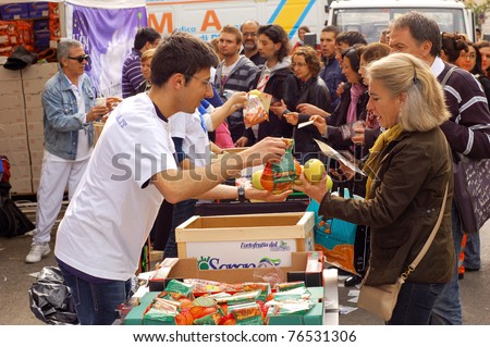 ROME, ITALY - MAY 1: Volunteers hand out snacks to people attending the beatification of Pope John Paul II in Rome, Italy on May 1, 2011. - stock photo