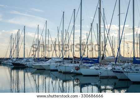 Rome, Italy - October 2015: Yachts and boats docked at the pier in the sea at the port of Rome in Italy at sunset in calm sunny weather and calm - stock photo