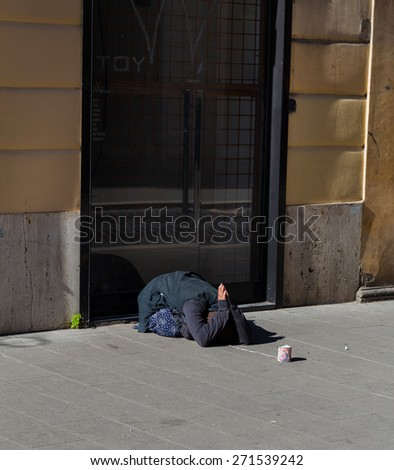 ROME, ITALY - 12TH MARCH 2015: A lady begging for money outside on a street in Rome