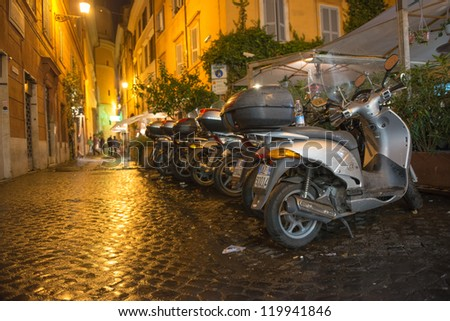ROME - NOV 1: Row of Scooters parked at night in the city center, November 1, 2012 in Rome. Scooter is the best and most used way to move in the city narrow streets - stock photo