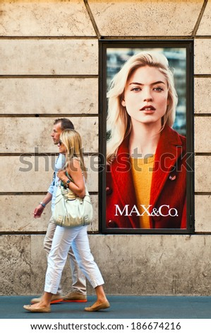 ROME - SEPTEMBER 18: unidentified couple walking past Max & Co. store ad at Via dei Condotti in Rome, Italy on September 18, 2013. Member of Max Mara launched in 1986 as the trendy youth division. - stock photo