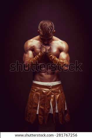 Rome warrior praying on the black background - stock photo