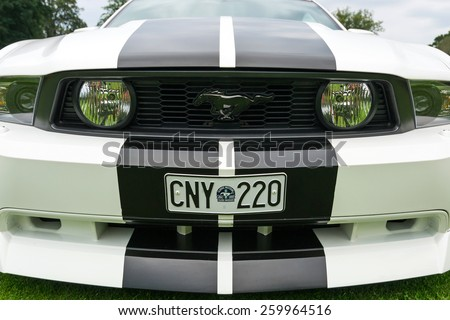 "RONNEBY, SWEDEN - AUGUST 09: Summer V8 car fans event ""Pony & muscle car meet"". Front close view of Ford Mustang model 2010 in 08 August, 2014 in Ronneby, Sweden. - stock photo"