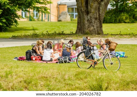 RONNEBY, SWEDEN - JULY 05, 2014: Several young women having picnic in the grass in public park. - stock photo