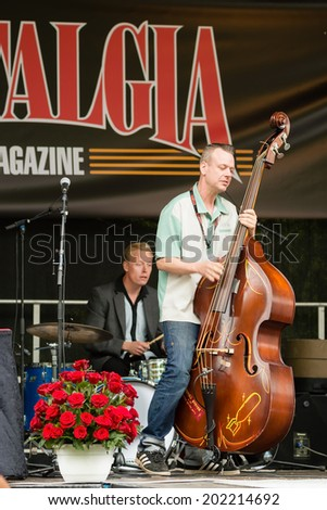 RONNEBY, SWEDEN - JUNE 28, 2014: Nostalgia Festival, classic cars, motorcycles, fashion and entertainment. Mikael Ek on double bass and Staffan Rigestam on drums. - stock photo