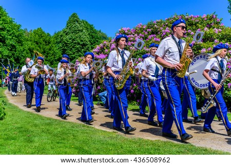 Ronneby, Sweden - June 6, 2016: The Swedish national day celebration in public park. Ronneby Skolorkester (school orchestra) marching through public park while playing.