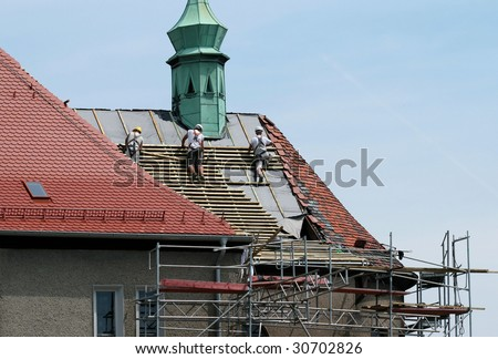 Roof construction works. Workers and scaffolding. Building renovation. - stock photo