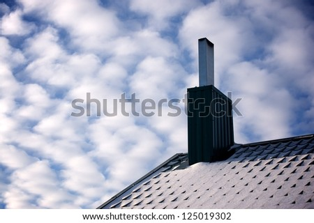 Roof covered with snow and chimney under beautiful blue sky with white clouds - stock photo