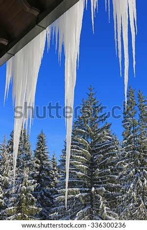 Roof icicles formed from snow on mountain house - stock photo