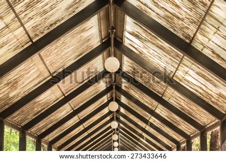 Roof made of glass and wood with row of lamps against sunshine  - stock photo