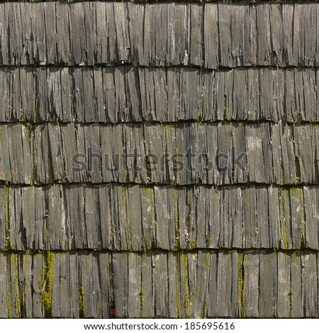 Roof made of rotting, grey planks with splintering edges and moss spots. - stock photo