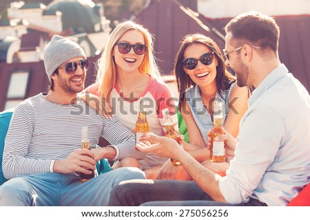 Roof party. Four young cheerful people chatting and drinking beer while sitting at the bean bags on the roof of the building - stock photo