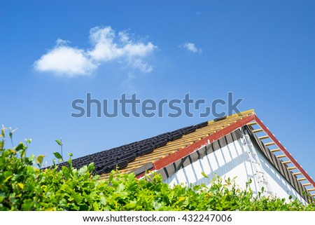 Roof renovation with black tiles in the summer - stock photo
