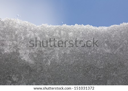 roof skylight window partially covered with melting snow; snow crystals especially in the lower part of image merge and grow larger during melting of snow; blue sky in the background. - stock photo