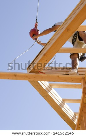Roof truss company placing new home wood engineered trusses on a residential construction site - stock photo