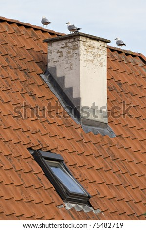 Roof with red tiling, dormer and chimney - stock photo