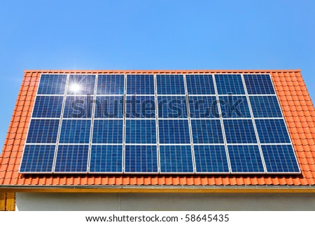 Roof with solar panel reflecting the sun, in the background a perfectly cloudless blue sky