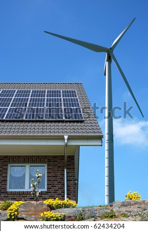 Roof with solar panels and wind turbines aside - stock photo