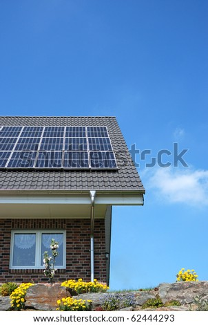 Roof with solar panels under blue sky - stock photo