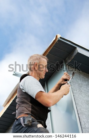 Roofer assembling a metal piece into the dormer wall on a sunny day - stock photo