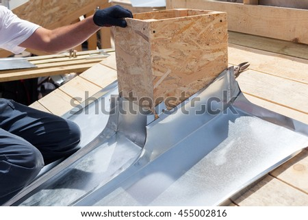 Roofer builder worker attach metal sheet to the chimney