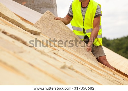 Roofer builder worker installing roof insulation material on new house under construction - stock photo