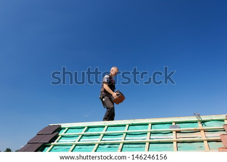 Roofer carrying tiles walking over the beams of a new roof