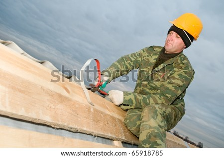 roofer cutting metal iron tiling with hand snips - stock photo