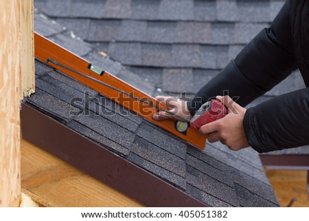 Roofer holding a tape measure and spirit level in his hands over newly installed tiles on a new build wooden house - stock photo