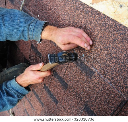 Roofer Install Bitumen Roof  Asphalt Shingles with Hammer - Closeup on Hands. Roofing Repair - stock photo