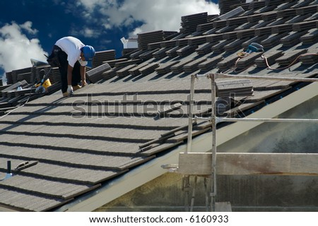 Roofer Laying Tile Shingles on a New Home - stock photo