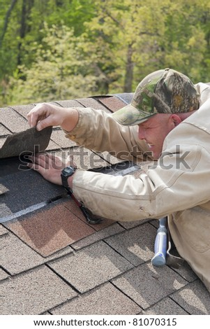Roofer repairing storm damage on customers home after strong wings and hail over night damaged roof - stock photo