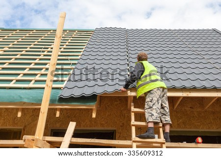 Roofer worker installing a metal tile on a new wooden house - stock photo