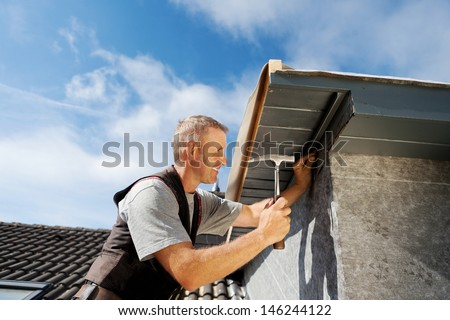 Roofer working on a new dormer by hammering nails into the roof edge - stock photo