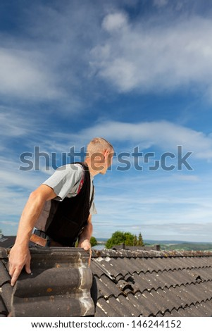 Roofer working on an old roof in a bright sunny day with a blue sky - stock photo