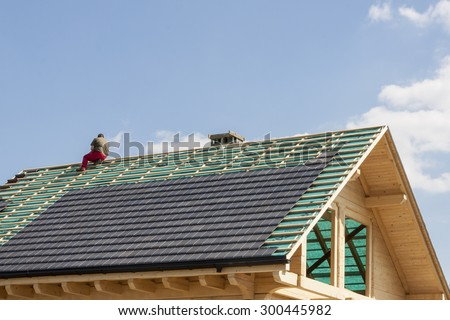 Roofer working on the top of the unfinished roof - stock photo