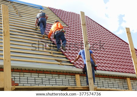 Roofers make the roof of metal tile - stock photo