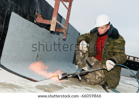 Roofing asphalt bitumen felt installation with heating and melting roll by torch on flame - stock photo