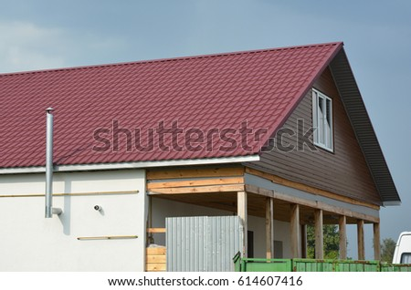 Roofing Construction with red metal roof tiles and metal chimney outdoors.